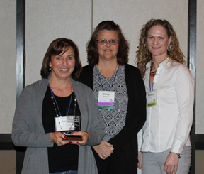 Photo of Lori Arndt holding her award with Cindy Schroeder in the center and Monica Helfer on the right