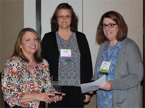 Photo of Peggy Kemp holding her award with Cindy Schroeder in the center and Vera Lynne Stroup-Rentier on the right
