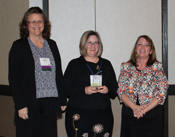 photo of Sarah Walters holding award with Cindy Schroeder and Peggy Kemp